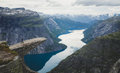 Trolltunga - famous rock formation and tourist famous hike, beautiful norwegian summer landscape with fjord, mountain and lake Royalty Free Stock Photo