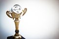 A trophy with a clock in side representing time management Royalty Free Stock Photos