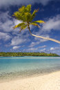 Tropical beach and lagoon aitutaki cook islands sandy shallow water with palm tree island in the distance one foot island Stock Photos