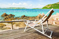 Tropical beach landscape with chairs for relaxation on wooden te Royalty Free Stock Photo