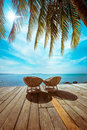 Tropical beach with palm tree and chairs amazing landscape for relaxation on wooden terrace travel background in vintage style Royalty Free Stock Images