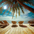 Tropical beach with palm tree and chairs for relaxation on woode amazing landscape wooden terrace travel background in vintage Stock Photo