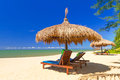 Tropical beach scenery with parasol and deck chairs in thailand Royalty Free Stock Images