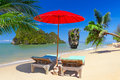 Tropical beach scenery with parasol and deck chairs Royalty Free Stock Photo