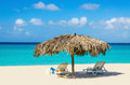 Tropical beach sunbeds and palm tree umbrellas amazing with golden sand azure water blue sky caribbean islands Stock Photos