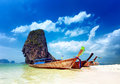 Tropical beach in thailand with traditional boats and rock Stock Images