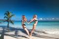 stock image of  Tropical beach, women having fun, jump love heart symbol