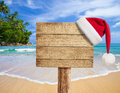 Tropical beach wooden signboard with Christmas hat Royalty Free Stock Images