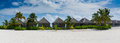 Tropical bungalos panorama view with white sand and palm trees at Maldives Royalty Free Stock Photo