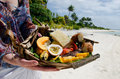Tropical food on deserted tropical island young woman hands carry of grilled fish fruits and vegetables dish served in aitutaki Royalty Free Stock Image