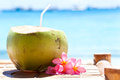 Tropical fresh cocktail on white beach coconut decorated plumeria Royalty Free Stock Photo