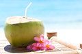Tropical fresh cocktail on white beach coconut decorated plumeria Royalty Free Stock Photos