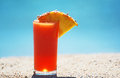 A tropical fruit drink on the beach refreshing glass of orange colored with slice of pineapple set with light blue back drop Stock Photo