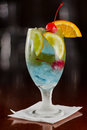 Tropical fruit punch cherries oranges light blue color served busy bar Royalty Free Stock Image