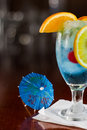 Tropical fruit punch cherries oranges light blue color served busy bar Royalty Free Stock Photos