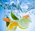 Tropical fruits fall deeply under water with a big splash Stock Image