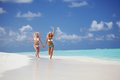 Tropical girls run two along the ocean coast Royalty Free Stock Photography