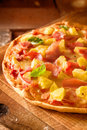 Tropical ham and pineapple pizza close up of a delicious on a thin crisp golden crust Royalty Free Stock Photo