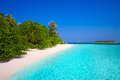 Tropical island with sandy beach with palm trees and turquoise c Royalty Free Stock Photo
