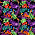 Tropical leaves, exotic flowers in neon glow. Repeating hawaiian pattern. Watercolor Royalty Free Stock Photo