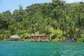 Tropical oceanfront property in panama with lush vegetation and house with hut over water caribbean sea central america Stock Photos
