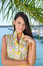 Tropical summer vacation beautiful girl smiling standing under a palm yachts and sea side on the background Royalty Free Stock Photos