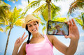 Tropical summer vacation selfie woman on caribbean travel taking photo young happy brunette on beach using her smartphone camera Royalty Free Stock Image