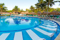 Tropical sunbeds in swimming pool Stock Photos