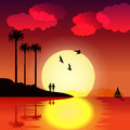 Tropical sunset with palm trees, birds, couple in love, boat and water reflection Royalty Free Stock Photo