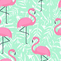 Tropical trendy seamless pattern with pink flamingos and mint green palm leaves. Royalty Free Stock Photo