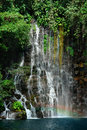 Tropical waterfall detail with rainbow.