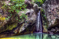 Tropical waterfall philippines a empties into a small pool in a forest on mindoro island in the green red and yellow mosses and Stock Images