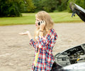 Trouble with the car engine, girl phoning to hep Stock Photo