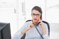 Troubled classy brown haired businesswoman answering the telephone in bright office Royalty Free Stock Image