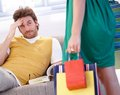 Troubled man and shopaholic woman Royalty Free Stock Photo