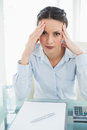 Troubled stylish brunette businesswoman holding her head and looking at camera in bright office Stock Images