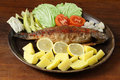 Trout oncorhynchus mikiss roasted with potatoes and vegetable garnish Royalty Free Stock Images