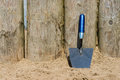 Trowel on the beach a is resting against some wooden poles a Stock Photos