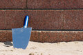 Trowel on the beach a is resting against stone wall a Royalty Free Stock Photos