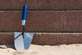 Trowel on the beach a is resting against stone wall a Royalty Free Stock Photo