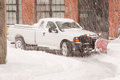 Truck plowing snow with snowplow attached working the street during a blizzard Royalty Free Stock Photography