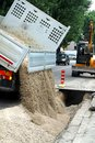 Truck tipper during the emptying of the gravel road during the e excavation work laying optical fibre conduits gas pipes Royalty Free Stock Photos