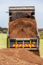Truck tipping sand earth soil from its large back bin photo image from rear and vertical close up Stock Photography
