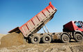 Truck unloading sand at construction site Royalty Free Stock Photos