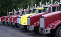 Trucks sitting in a row lined up ready to haul logs out of the mountains of the pacific northwest Stock Images