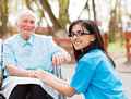 Trust beautiful doctor nurse in blue coat walking a kind elderly lady in wheelchair in park Royalty Free Stock Photo
