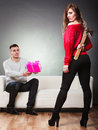 Trusting guy giving present to misleading girl false feelings relations problem pink box insincere women holding axe behind her Stock Photo