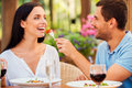Try my meal handsome young men feeding his girlfriend with salad and smiling while both relaxing in outdoors restaurant Royalty Free Stock Image