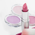 Tube of pink lipstick in a makeup set open beautiful modern with eye shadow visible behind matching colors focus to the Stock Images