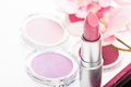 Tube of pretty pink lipstick with matching eye shadow and blusher in a beauty background with focus to the Royalty Free Stock Images